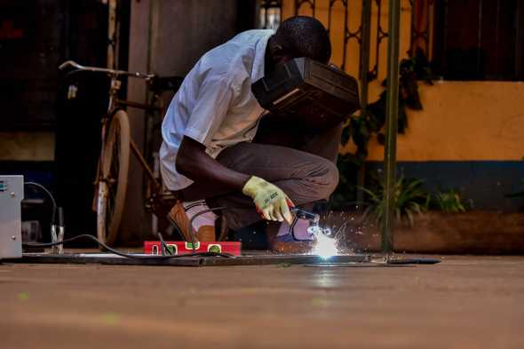 Jeremiah Brian Nkuutu welds an ambulance carrier. The ambulances are constructed in Uganda with locally sourced materials and by locals. [Nicholas Bamulanzeki/Al Jazeera]
